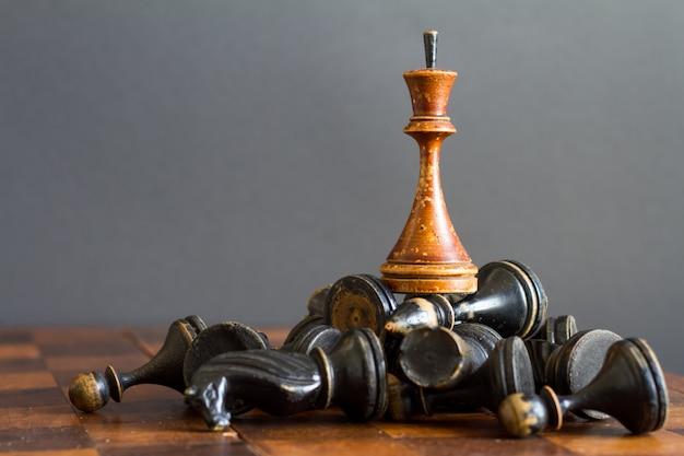Hölzerne schachfiguren der weinlese auf einem alten schachbrett, selektiver fokus.