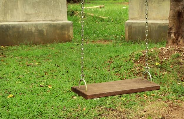 Hölzerne schaukeln der leeren kette auf aktivitätsyard im allgemeinen park.