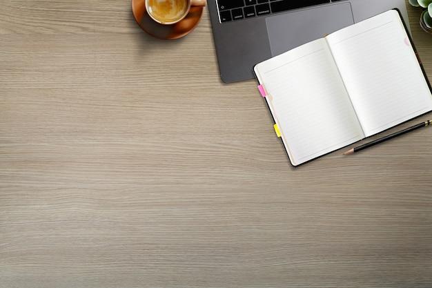 Hölzerne schreibtischtabelle der draufsicht mit laptop-computergeräten und -versorgungen.