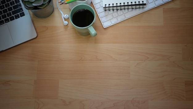 Hölzerne schreibtischtabelle des büros mit laptop-computer, büroartikel und kopienraum