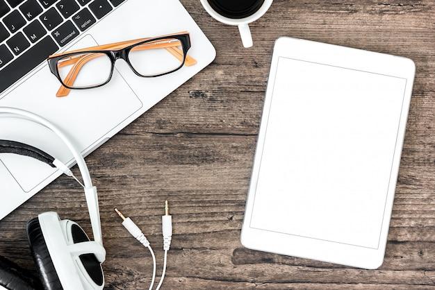 Hölzerne schreibtischtabelle und -ausrüstung browns für das bearbeiten und hörende musik mit weißer tablette des kopfhörers und des weißen leeren bildschirms im draufsicht- und kopienraum.