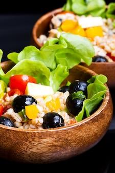 Hölzerne schüssel mit dinkel-salat mit oliven und tomaten