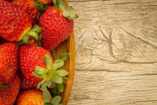 Hölzerne schüssel mit erdbeeren am hölzernen hintergrund