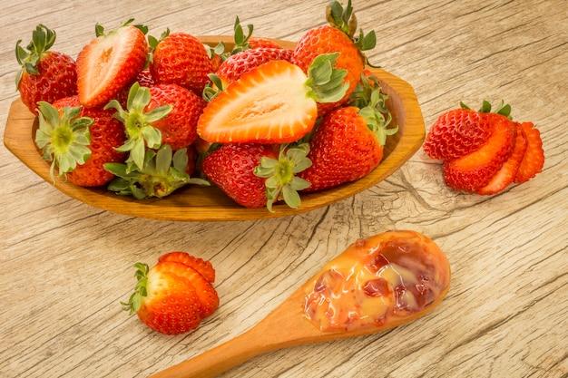 Hölzerne schüssel mit erdbeeren und dulce de letche im löffel am hölzernen hintergrund