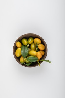 Hölzerne schüssel mit gelben kumquats mit blättern auf weiß.