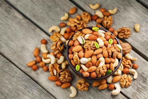 Hölzerne schüssel mit mischnüssen auf einem hölzernen grau. walnuss, pistazien, mandeln, haselnüsse und cashewnüsse, walnuss.