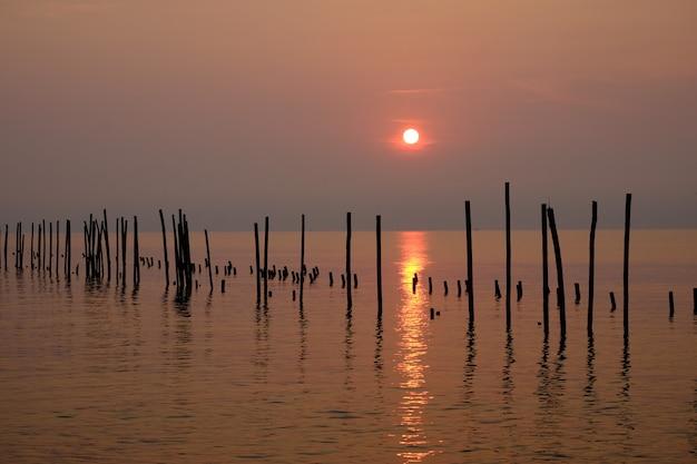 Hölzerne stapel rudern im meer in der sonnenaufgangzeit.