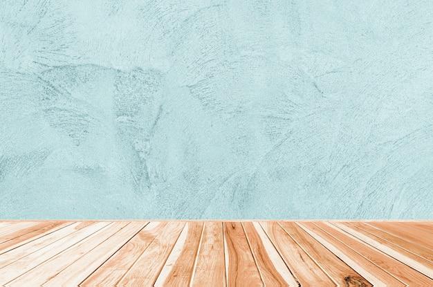 Hölzerne tabelle auf abstraktem schmutz-dekorativem rauem ungleichem marine-blau-stuck-wand-hintergrund: innenarchitektur oder montage zeigen ihr produkt an