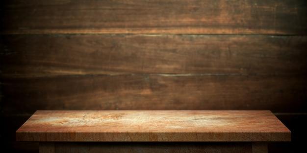 Hölzerne tabelle auf dunkelbrauner wand unscharfer hintergrund.