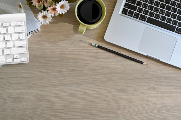 Hölzerne tabelle des spitzenbüros mit tasse kaffee, notizbuch, bleistift, laptop und kopienraum