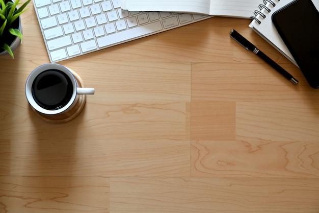 Hölzerne tabelle des spitzenbüros mit tasse kaffee, notizbuch, bleistift, tastatur und kopienraum
