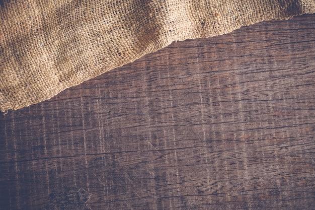 Hölzerne tabelle mit alter sackleineneinwand-tischdeckenbeschaffenheit mit filtereffekt-weinleseart