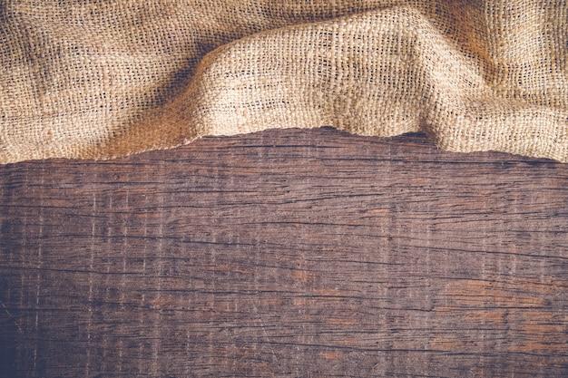 Hölzerne tabelle mit alter sackleineneinwand-tischdeckenbeschaffenheit