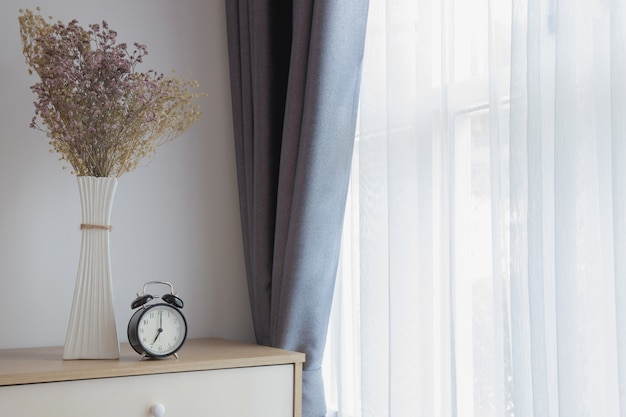 Hölzerne tabelle mit dekoration blüht auf weißem vorhangfenster-beschaffenheitshintergrund.