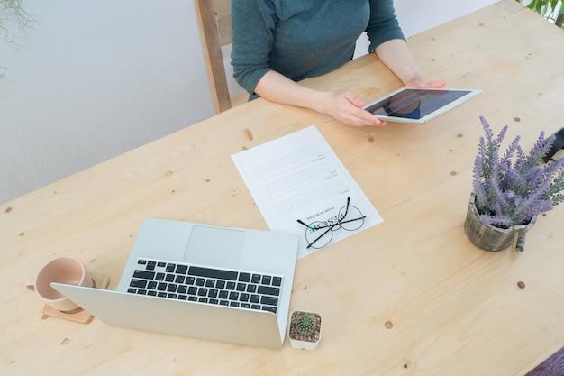 Hölzerne tabelle mit der menschlichen hand unter verwendung des smartphone, der tablette, des handys mit zusammenfassungsinformationen.