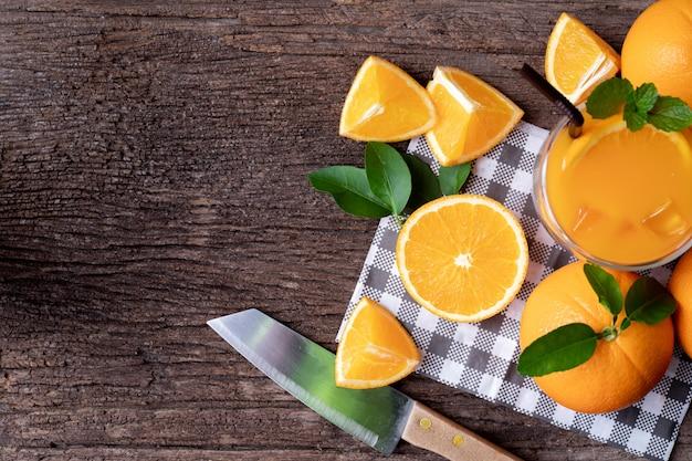 Hölzerne tabelle mit frischer geschnittener orange frucht und glas orangensaft.