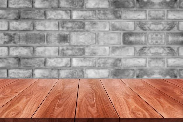 Hölzerne tabelle vor backsteinmauerunschärfehintergrund.