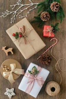Hölzerne tabellenplanke verzieren mit vieler schönen geschenkbox, kiefernblättern und kiefernkegeln, zuckerstange im weihnachtskonzept