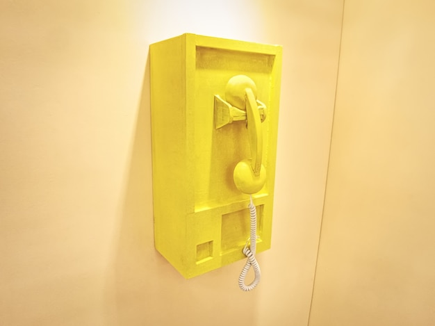 Hölzerne telefon-konzeptbox im retro-stil an gelber wand montiert
