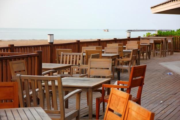 Hölzerne terrasse mit holztisch und schreibtisch auf strand am seeansichtpunkt