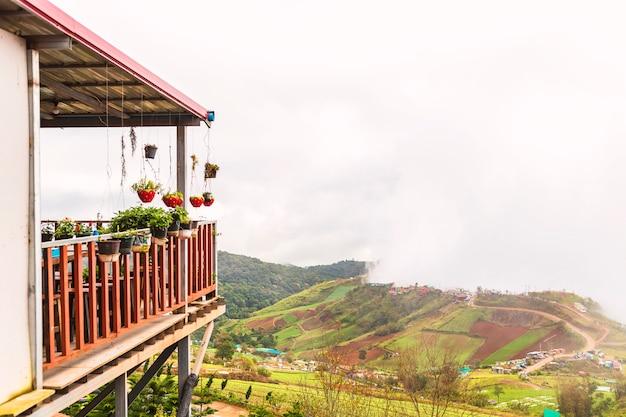 Hölzerne terrasse mit morgennebelansichten in ländliche gebiete von thailand.