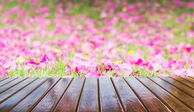 Hölzerne terrasse über schönem purpurrotem blumenhintergrund