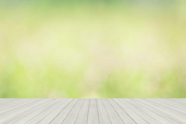 Hölzerne tischplatte an mit unschärfeglasfenster-wandhintergrund