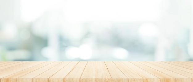Hölzerne tischplatte an mit unschärfeglasfensterwandhintergrund.