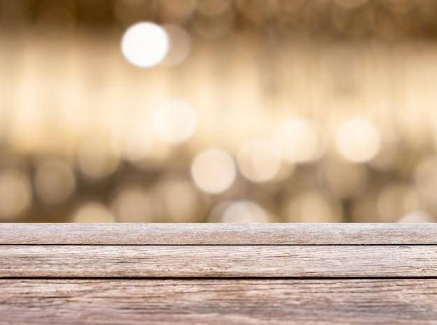 Hölzerne tischplatte auf abstraktem goldbokeh hintergrund