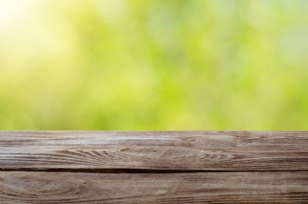 Hölzerne tischplatte auf glänzendem bokeh-grün