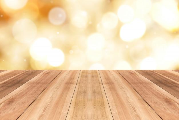 Hölzerne tischplatte auf schimmer glänzendem gold-bokeh zusammenfassungshintergrund