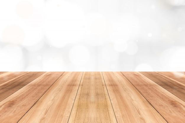Hölzerne tischplatte auf schimmer glänzendem weißem bokeh zusammenfassungshintergrund