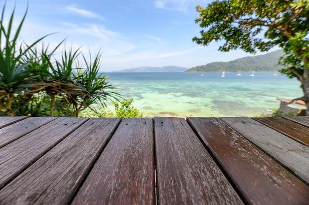 Hölzerne tischplatte auf tropischem meer im sommer