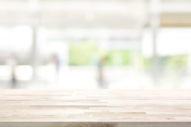 Hölzerne tischplatte auf unschärfeküchenfenster