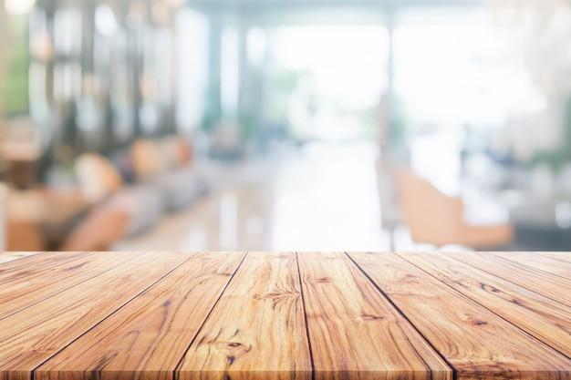 Hölzerne tischplatte auf unscharfem innenaufnahmehotel oder moderne halle für hintergrund