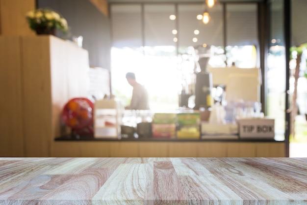 Hölzerne tischplatte auf unscharfem restaurant- oder kaffeestubehintergrund