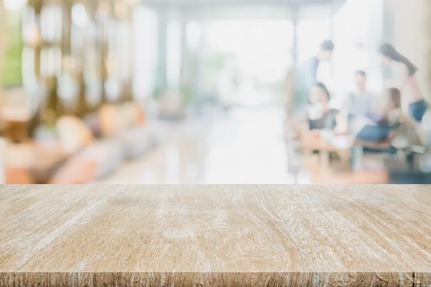 Hölzerne tischplatte auf verschwommenen innenaufnahmehotel- oder flurmontageprodukten