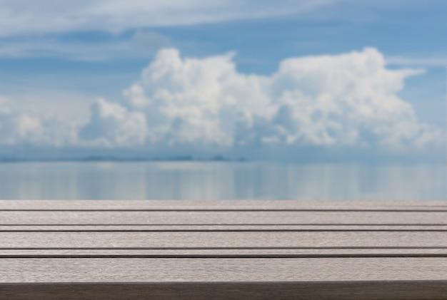Hölzerne tischplatte der planke mit unscharfem sommerhintergrund des blauen seehimmels