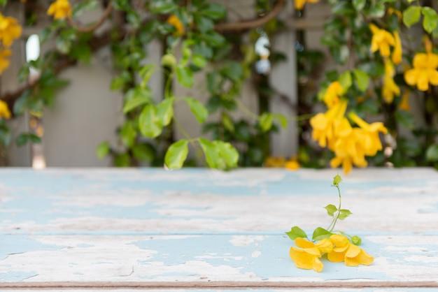Hölzerne tischplatte der weinlese mit schönen gelben blumen und grünblättern