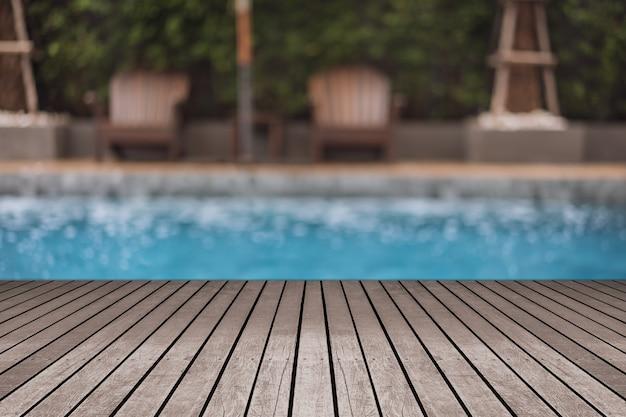 Hölzerne tischplatte in im freien mit unschärfeswimmingpool- und -strandstuhlhintergrundsommerferienkonzepten.