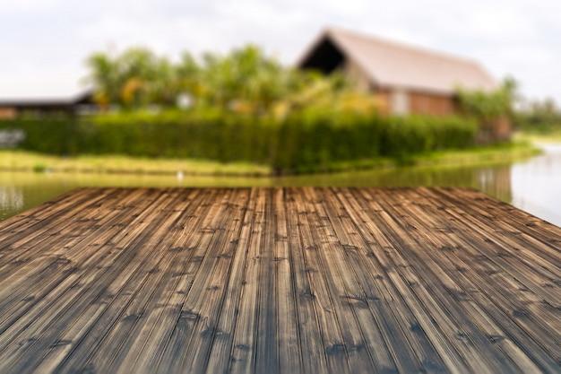 Hölzerne tischplatte lokalisiert auf unschärfehaus im landhintergrund