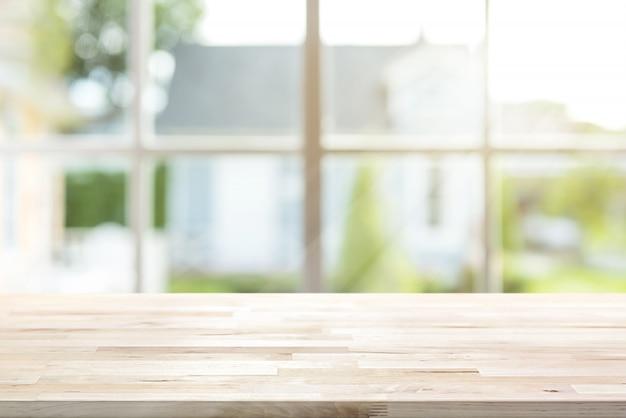 Hölzerne tischplatte mit fenster und morgensonnenlicht im hintergrund
