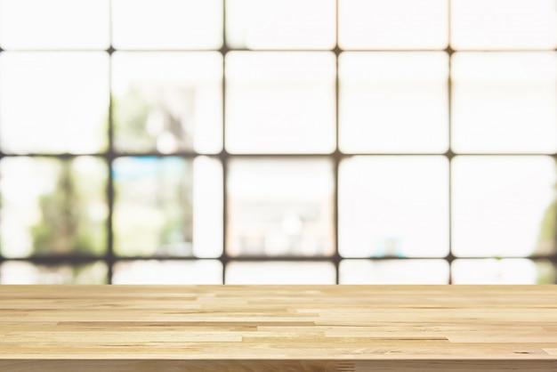 Hölzerne tischplatte mit hellem quadratischem transparentem fenster der unschärfe des cafés im hintergrund