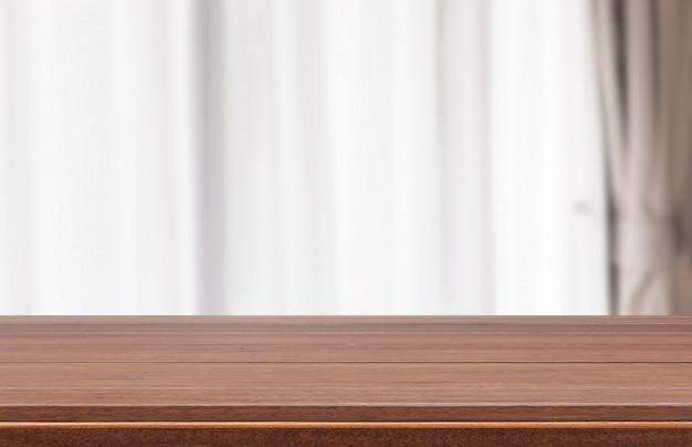 Hölzerne tischplatte mit modernem weißem vorhangraumhintergrund