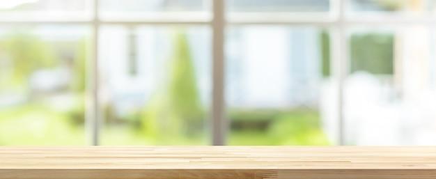 Hölzerne tischplatte mit unschärfefahnenhintergrund des grünen gartens außerhalb des fensters
