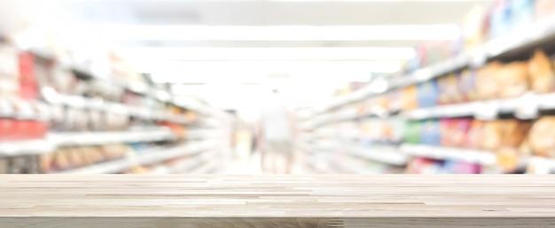 Hölzerne tischplatte mit unschärfesupermarkt im hintergrund, panoramische fahne