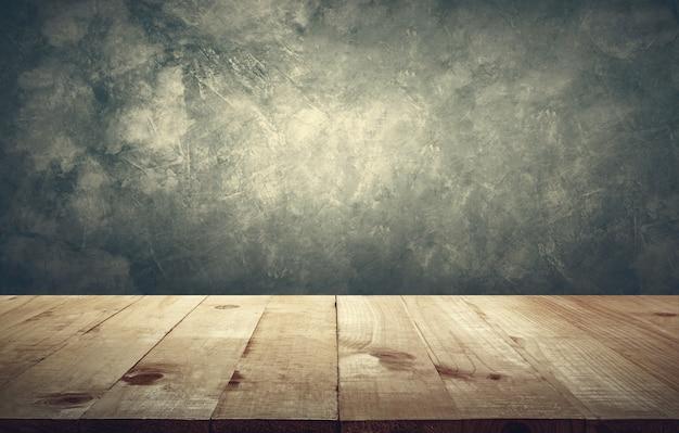 Hölzerne tischplatte mit weinleseschmutz-zementwandhintergrund