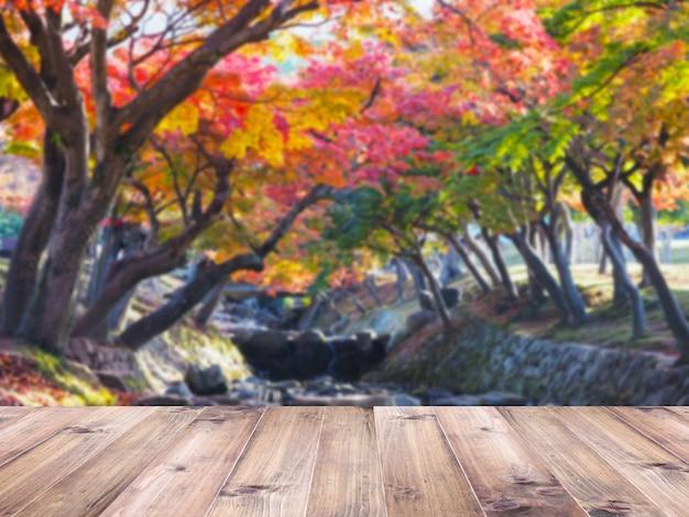 Hölzerne tischplatte über undeutlichem buntem ahornblattbaum am herbstparkhintergrund in japan.