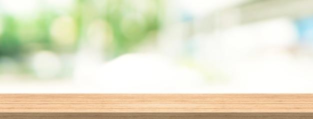 Hölzerne tischplatte und unschärfehintergrund für produkt- und anzeigenmontagefahnengröße
