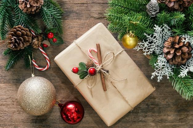Hölzerne tischplatte verzieren mit kiefernblättern und kiefernkegeln, stechpalmenbällen, ball oder flitter und geschenkbox im weihnachtskonzept